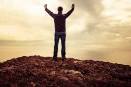 Man on mountain with hands in air, nothing in front of him