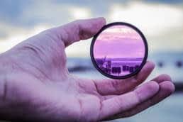 Sexually adventurous; Hand holding up purple lens